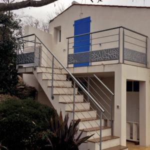 """Habillage d'un escalier droit extérieur en béton (marches carrelées) d'accès à une terrasse d'un particulier. Rampe : poteaux métalliques plats tournés, main courante cylindrique métal et lisses droites métalliques. Garde corps : main courante cylindrique, poteaux métalliques plats tournés,lisses droites métalliques et soubassement tôle style """"Algues""""."""