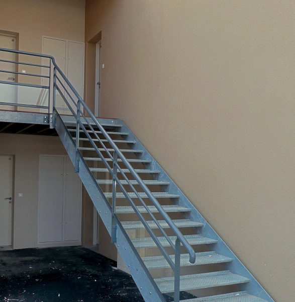 Escalier extérieur en métal galvanisé sans contremarches. Marches tôles métal perforées antidérapantes. Rampe et garde corps : main courante cylindrique, poteaux plats, lisses métalliques droites et soubassement en verre.