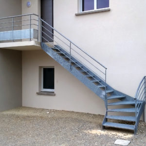 Escalier extérieur quart tournant bas en métal galvanisé. Marches perforées. Rampe : main courante et lisses cylindriques. Garde corps : main courante et lisses cylindriques droites et coudées, soubassement tôle perforée.