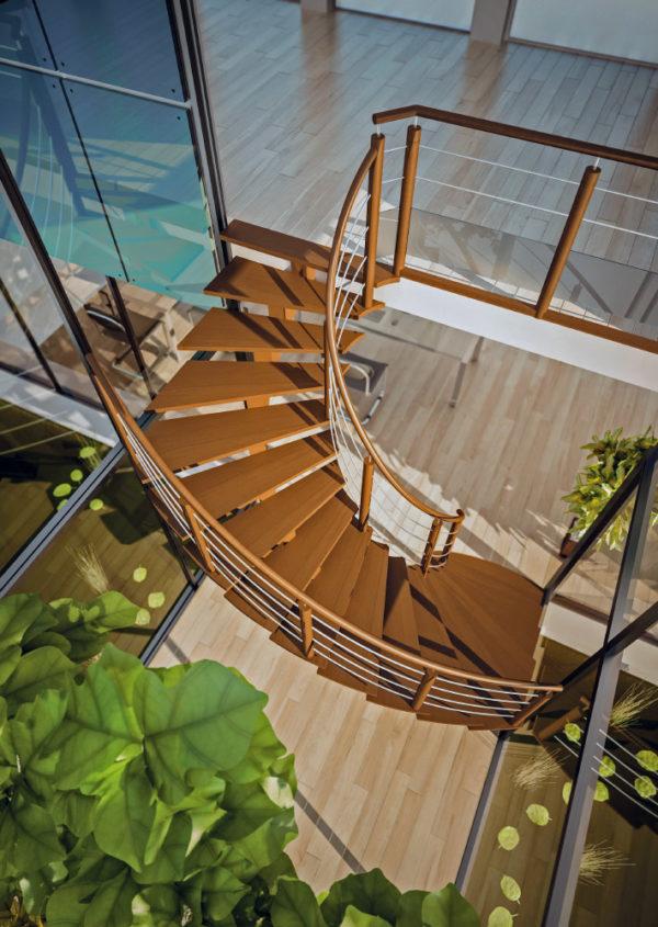 Escalier hélicoïdal en bois sans contremarches de teinte chêne moyen. Crémaillère débillardée avec fût central. Poteaux et main courante cylindriques lisses façon Alitex. Lisses inox courbes type tubes