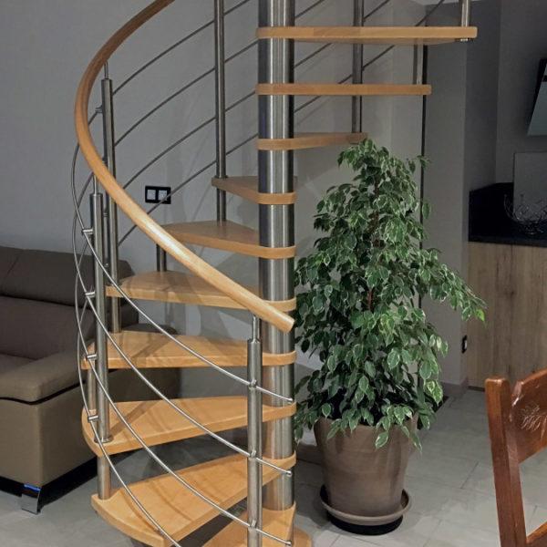 Escalier hélicoïdal (colimaçon) en bois (teinte chêne clair) et métal, sans contremarches. Noyau central en métal brillant, marches en bois. Main courante en bois rond. Poteaux et pitons et lisses métal en acier inox.