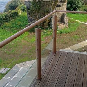 Garde corps d'un escalier en bois Iroko de teinte naturelle d'une maison en bord de mer. Lames striées, poteaux et main courante cylindriques. Pitons et lisses en inox. Soubassement en verre.
