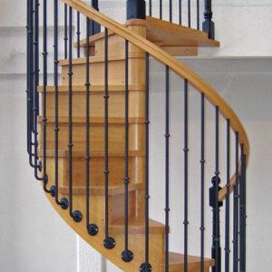 Escalier en bois hélicoïdal (colimaçon) teinte chêne clair avec contremarches. Rampe : main courante en bois teinte chêne clair avec gorges, balustres en fer forgé teinte noire avec débords, poteaux bois et métal noirs forgés.