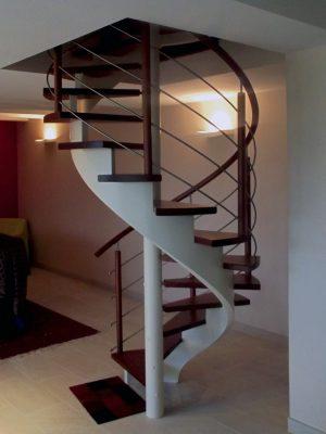 Escalier hélicoïdal (colimaçon) en bois sans contremarches. Noyau et limon central blancs. Poteaux, marches et main courante teinte merisier. Pitons et lisses métal type tubes inox.