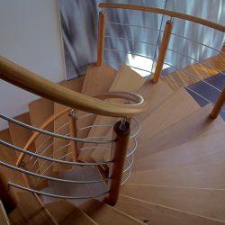 Escalier hélicoïdal / colimacon, sans contremarches, en bois teinte merisier. Poteaux, rampe, main courante ronds, pitons et lisses en métal tiges tubes inox