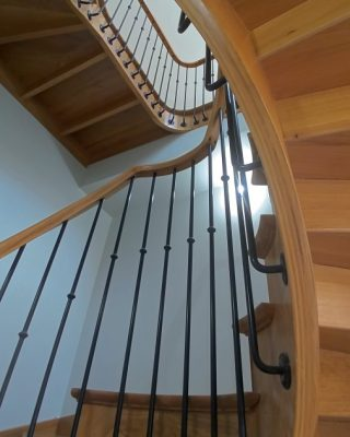 Escalier en bois teinte chêne clair, double quart tournant, avec contremarches et palier intermédiaire. Rampe : main courante en bois teinte chêne clair, demi ronds avec gorge sur balustresavec débord noires en métal.