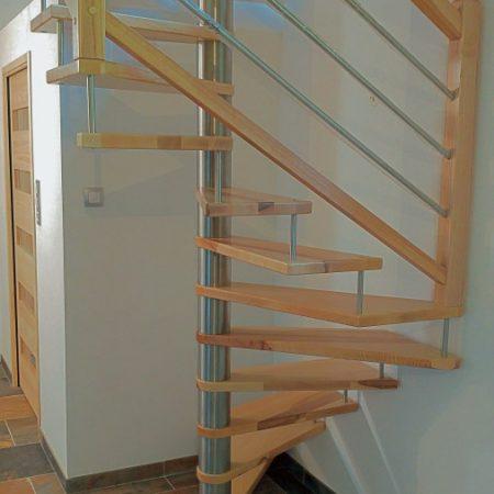 Escalier hélicoïdal / colimaçon en bois teinte chêne clair vernis. Escalier sans contremarches, de forme carrée suivant un noyau central rond avec entretoises métal type inox. Rampe : main courante courante standard sans gorge, poteaux standards et lisses droites en métal type tubes inox.
